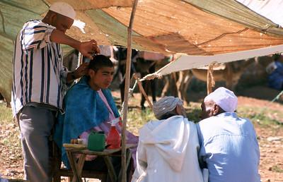 MOROCCO 2003/ 019 Markttafereel in Souk De Foum Jeema. Een kapper aan 't werk.