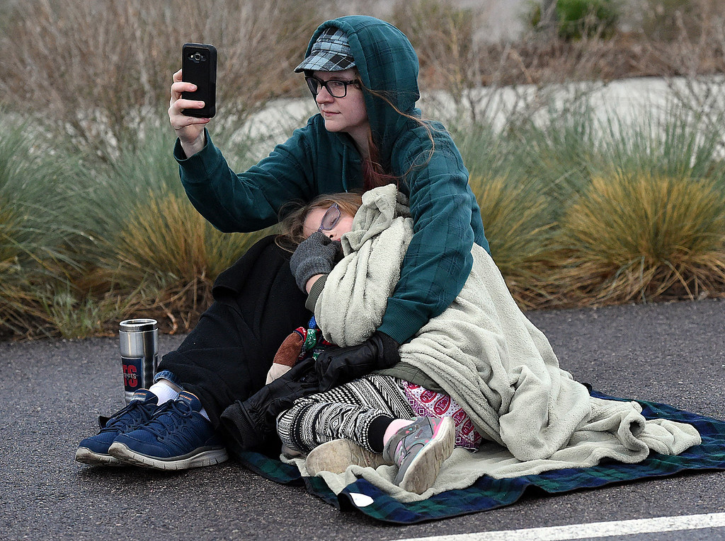 . Trying to stay warm under blankets as the sun rises, Ellie Falter and her daughter, Lillianna Falter, 6, both of Westminster, watch a take photos of The Maroon Bells Morris Dancers and the Breathless in Berthoud Border Morris dancer as they dance the sun up on Tuesday, May 1, 2018, May Day -- a tradition dating back to the 1500s -- as they celebrate traditions from the Cotswalds region on England.  (Photo by Jenny Sparks/Loveland Reporter-Herald)