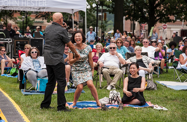 Mike Pender helps Keiko James  to her feet to dance during the performance of the Air Force band.  Seated is her friend Hiromi Kawamoto (in black dress) .