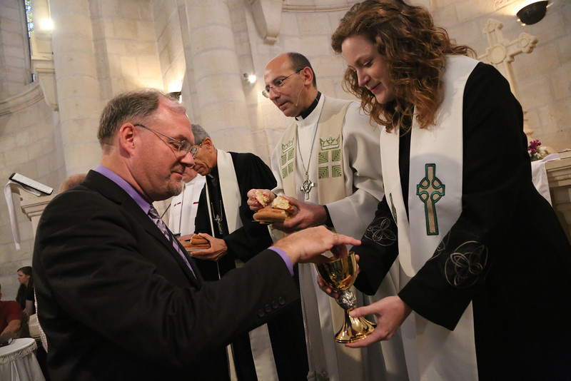 Doug Dicks receives communion from Kate Taber