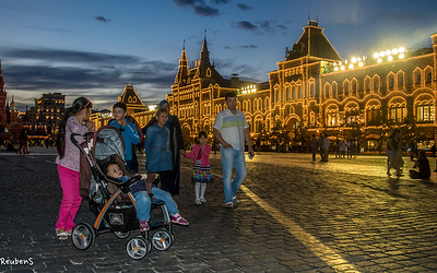 Family on Red Square in front of lit up GUM, a large high end shopping arcade