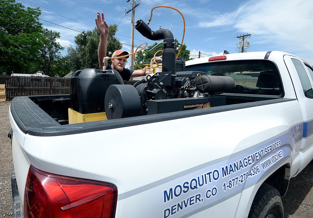 . Will Schlatmann, assistant manager at Vector Disease Control International\'s downtown Loveland office, explains Thursday, June 7, 2018, how the ultra low volume fogging machine in the back of a truck works to spray for mosquitos.  (Photo by Jenny Sparks/Loveland Reporter-Herald)