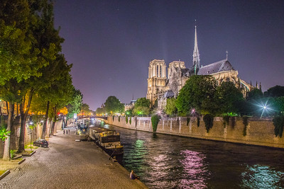 Seine River and Notre Dame Cathedral with people mulling around on a Friday night, Paris, France