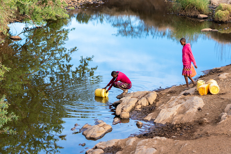 Kenyan women gather water from the local river