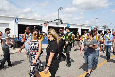 Kyle Busch and Samantha walking and filming by the pits and garages on the way to the car