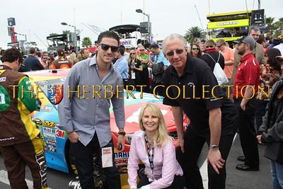 Matt Klarberg, Sara Herbert-Galloway and Barry Klarberg by Kyle Busch's M&M car