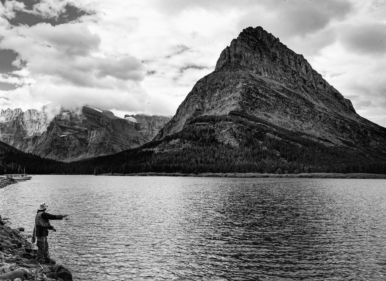 Fisherman at Many Glacier Lake b&w