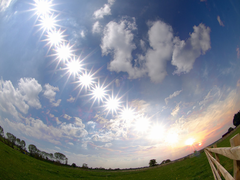 18 May 2014. Sun passage over Leicestershire skies during the 9 hr period between 1130hrs and sunset (2030hrs). What you are looking at is a composite image of the sun as depicted by Earth's rotation, with images captured throughout the entire period. Captured with Olympus E5 & 8mm fisheye.  How did I capture this? - I set up camera on tripod and calculated where the Sun would rise and set in respect of my composition (note the fence line leading the eye to the final sunset). Using an external time lapse controller (set to snap away every 60s) I commenced at 1130hrs through till sunset, approx 2030hrs. To create the starburst effect I set the aperture to a high F22, ISO 200 and let the camera snap away continuous. Once complete I imported all images into MAC and brought together all of the Suns, separated by 40min interval, within StarStax software.  The final composite is shows the effect of Earth's rotation through the sun :-)