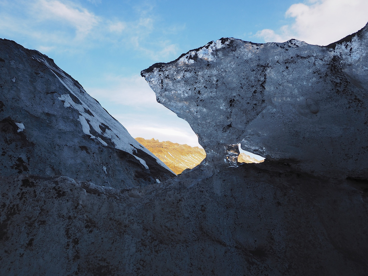 Glacier, Solheimajokull. Olympus E-M1, 12mm m4/3 lens. F3.2, 1/800s, ISO 200. Whilst walking on the glacier came across this chunk of ice wall with a few windows. The ice was caked with black volcanic ash and the bright sky offered a testing dynamic range capture. I focused on the green land/mountain using the touch lcd screen, another great feature allowing to compose and focus together.