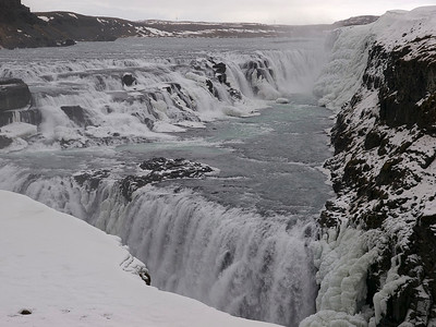 "Gullfoss (Golden Falls) is a massive waterfall located in the canyon of Hvítá river in southwest Iceland.  It is is one of the most popular tourist attractions in the country. The wide Hvítá rushes southward and 1km above the falls it turns sharply to the left and flows down into a wide curved three-step ""staircase"" and then abruptly plunges in two stages into a crevice 105 ft deep. The crevice is 60 ft wide, and 2.5 km in length, is at right angles to the flow of the river.   The part frozen falls took my breath away as I first approached. Spectacular is just not grand enough to describe it. I trust the pictures help. Nice shot of the stair step. Olympus E3, 12-60mm SWD."