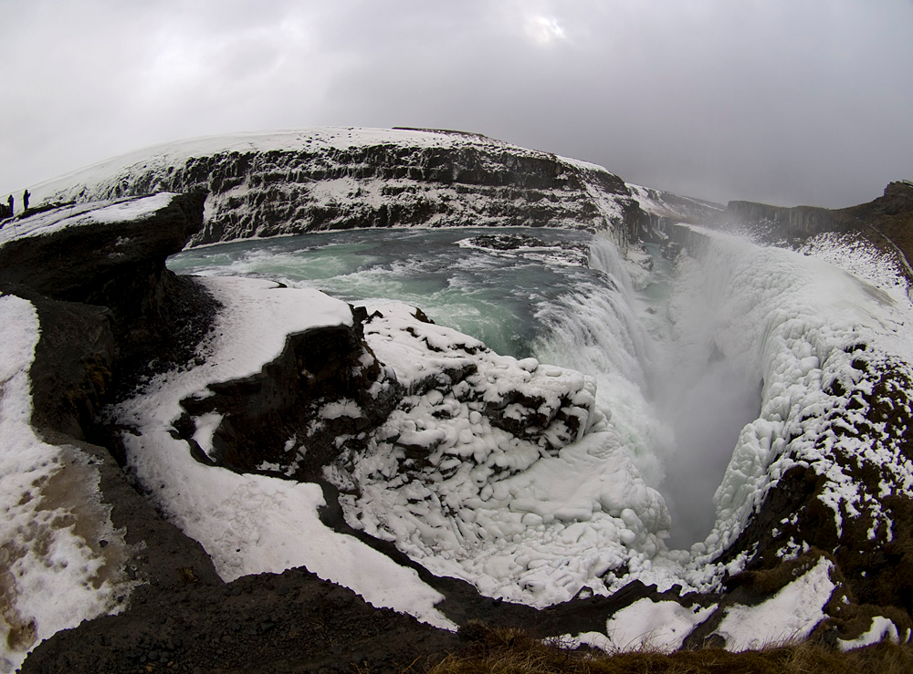 """Gullfoss (Golden Falls) is a massive waterfall located in the canyon of Hvítá river in southwest Iceland.  It is is one of the most popular tourist attractions in the country. The wide Hvítá rushes southward and 1km above the falls it turns sharply to the left and flows down into a wide curved three-step """"staircase"""" and then abruptly plunges in two stages into a crevice 105 ft deep. The crevice is 60 ft wide, and 2.5 km in length, is at right angles to the flow of the river.   The part frozen falls took my breath away as I first approached. Spectacular is just not grand enough to describe it. I trust the pictures help. Olympus E3, 8mm fisheye."""