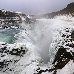 """Gullfoss (Golden Falls) is a massive waterfall located in the canyon of Hvítá river in southwest Iceland.  It is is one of the most popular tourist attractions in the country. The wide Hvítá rushes southward and 1km above the falls it turns sharply to the left and flows down into a wide curved three-step """"staircase"""" and then abruptly plunges in two stages into a crevice 105 ft deep. The crevice is 60 ft wide, and 2.5 km in length, is at right angles to the flow of the river.   The part frozen falls took my breath away as I first approached. Spectacular is just not grand enough to describe it. I trust the pictures help. Olympus E3, 12-60mm SWD."""