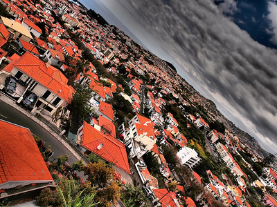 April 25 2011. Madeira is a beautiful country. This was captured in the capital Funchal whilst riding on the cable car to the mountain top using the Oly E5 dramatic tone art filter. The orange tile roof building really exacerbated by the art filter.