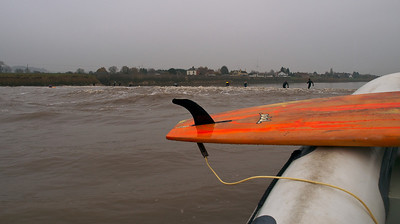 Severn Bore with surfers ahead of the loaded inflatable.