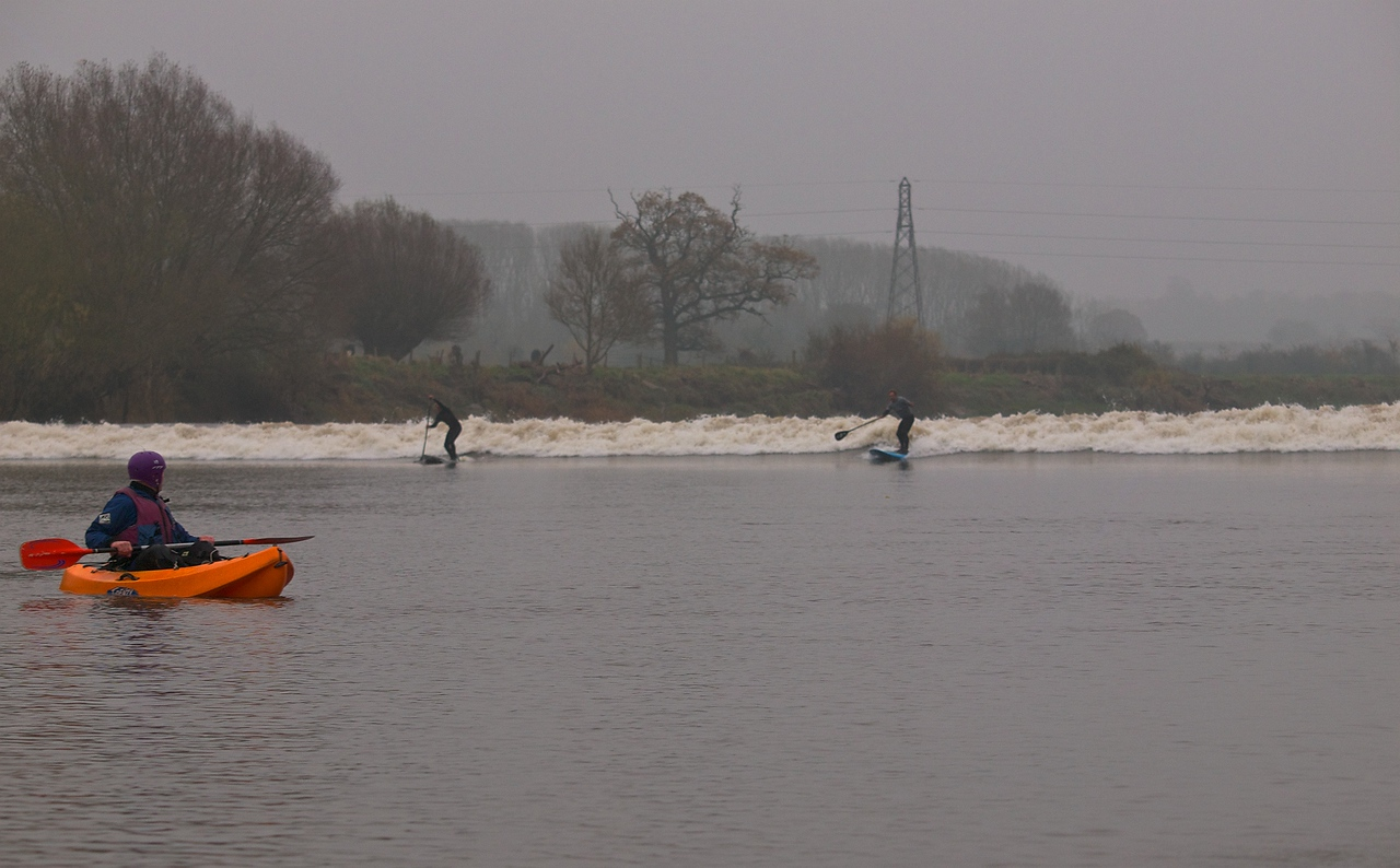 Wider shot showing the bore wave with surfers.