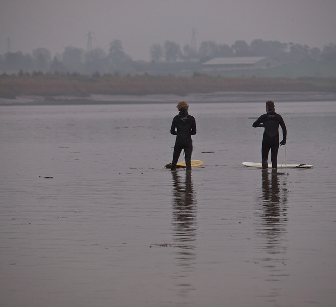 Surfers await the bore arrival.