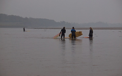 Surfers wait at numerous locations along the river, ahead of the bore.