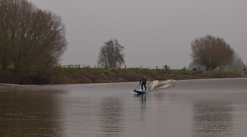 A lonely surfer enjoys the bore as it starts to build well here.