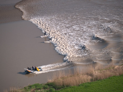 In 2007 I experienced the Severn Bore from a vantage point like no other, the sky. I persuaded a microlight pilot to take me up in the air to follow the tidal bore. I had never been in a microlight before. When I arrived at the airfield in Gloucester the microlight reminded me of 'Little Nellie' from the James Bond film 'You Only Live Twice'.   We accelerated over a bumpy field and then all of a sudden we swept upwards, turning at the same time. All too quickly houses turned into tiny boxes and roads turned into lines. The view was amazing. The Severn river became the dominant feature from the sky, snaking around the numerous towns before disappearing into the horizon towards the Severn Bridge. It may have been a pleasant 14C on the ground but 500ft in the air it was near freezing! A few minutes later I had a sighting of the bore.   It barely appeared as a ripple at this height but I immediately sprung the camera into action. Over the course of the next hour and a half I got some spectacular footage. I was amazed at how much the bore changes in appearance through the differing sections of the river. At times we were struggling to see the leading edge, no more than a ripple. Then out of nowhere a huge breaking wave would appear and rip all in its path. My hands were frozen solid after about 15 mins into the flight. There were also a few 'white knuckle' moments as we twisted, turned and dived in one manoeuvre. I was close to chucking on more than one occasion. I eventually landed and I was visibly shaking such was the adrenalin running through me. It was an unbelievable shoot, the toughest I have ever undertaken in very testing conditions for a camera (Olympus E1, 90-250mm lens). The aerial images over the next few pages made most of the National newspapers the next day.