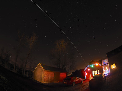 Festive ISS 22 Dec 2013. The International Space Station (ISS) flies over East Midlands (1759hrs flyby).  A very bright flyby passing from the west to east with a festive combo :-)  How did I capture this? - Camera (Olympus E-M1) with fisheye lens (Oly 8mm) set on tripod. I aligned the west horizon with the Christmas decos to ensure it would originate over. Setting camera in manual mode, f3.5, ISO 320 & 10s exposure time & using remote cable to shoot continuous for approx a dozen or so shots. The garage and trees given a bit of illumination from painting with a torch. Once complete I imported all images & stacked in software to produce this composite image.