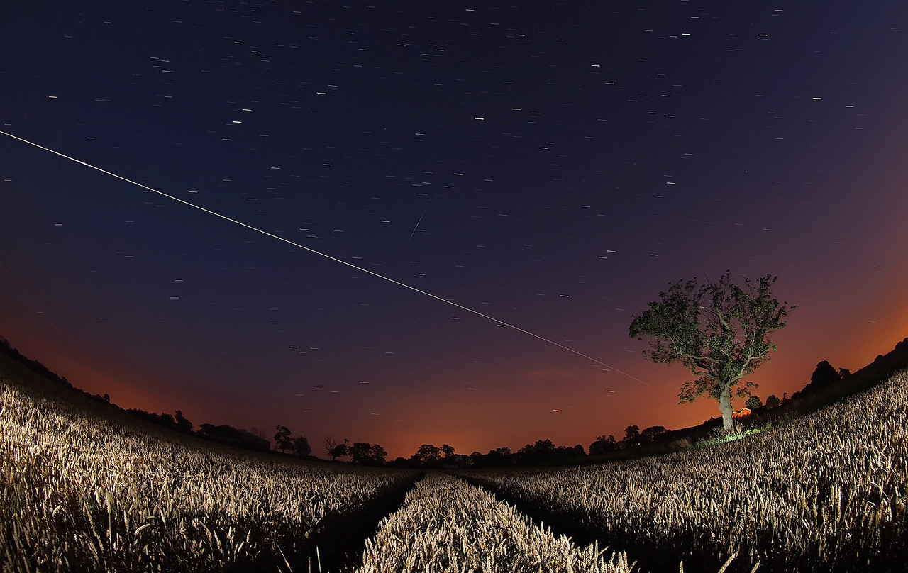 August 8th 2012. Summer ISS passes are back over UK evening skies & what a sight to kick them off. A rare clear sky evening and the 2207hrs flyby moving from the SW to E skies was a super bright event. I selected a nearby corn field which provided a great foreground composition. Lit with some remote flash bursts. Note the Iridium Flare 11 in the middle of image just above the ISS trail. It nearly intersected :-) Captured with Oly E5, 8mm fisheye. Numerous 15s exposures, F3.5 and composite stacked with StarStax software.