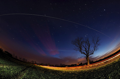 Christmas Day ISS 25 Dec 2013. The International Space Station (ISS) flies over East Midlands (1711hrs flyby).  A very bright flyby over rural field in East Mids.  How did I capture this? - Camera (Olympus E-M1) with fisheye lens (Oly 8mm) set on tripod. I located the camera in a field and composed around the tree, knowing the ISS would pass over from west to east. Setting camera in manual mode, f3.5, ISO 320 & 10s exposure time & using remote cable to shoot continuous for approx a dozen or so shots. The field was painted with a few flash bursts, although a passing car completed the job for me :-)  Once complete I imported all images & stacked in software to produce this composite image.