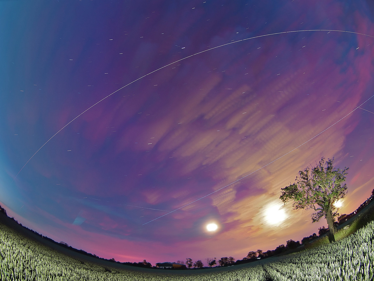 June 13/14 2011. Another amazing marathon night of multiple ISS flybys across UK skies. Once again the ISS flew over 4 times. What is amazing about this shot is that I have captured on camera all 4 passes. Not sure this has ever been done before! Flyby times 2243, 0018, 0153 & 0329 hrs. Some cloud cover rolling in prevented the almost perfect shot. Still beggars can't be choosers.  Why are we getting so many ISS passes in one day? Universe Today Captured with Oly E5 & 8mm fisheye.  Camera settings: 15s exposures shot continuous during flyby, ISO 500, F3.5. Foreground lit with a few flash bursts away from camera.