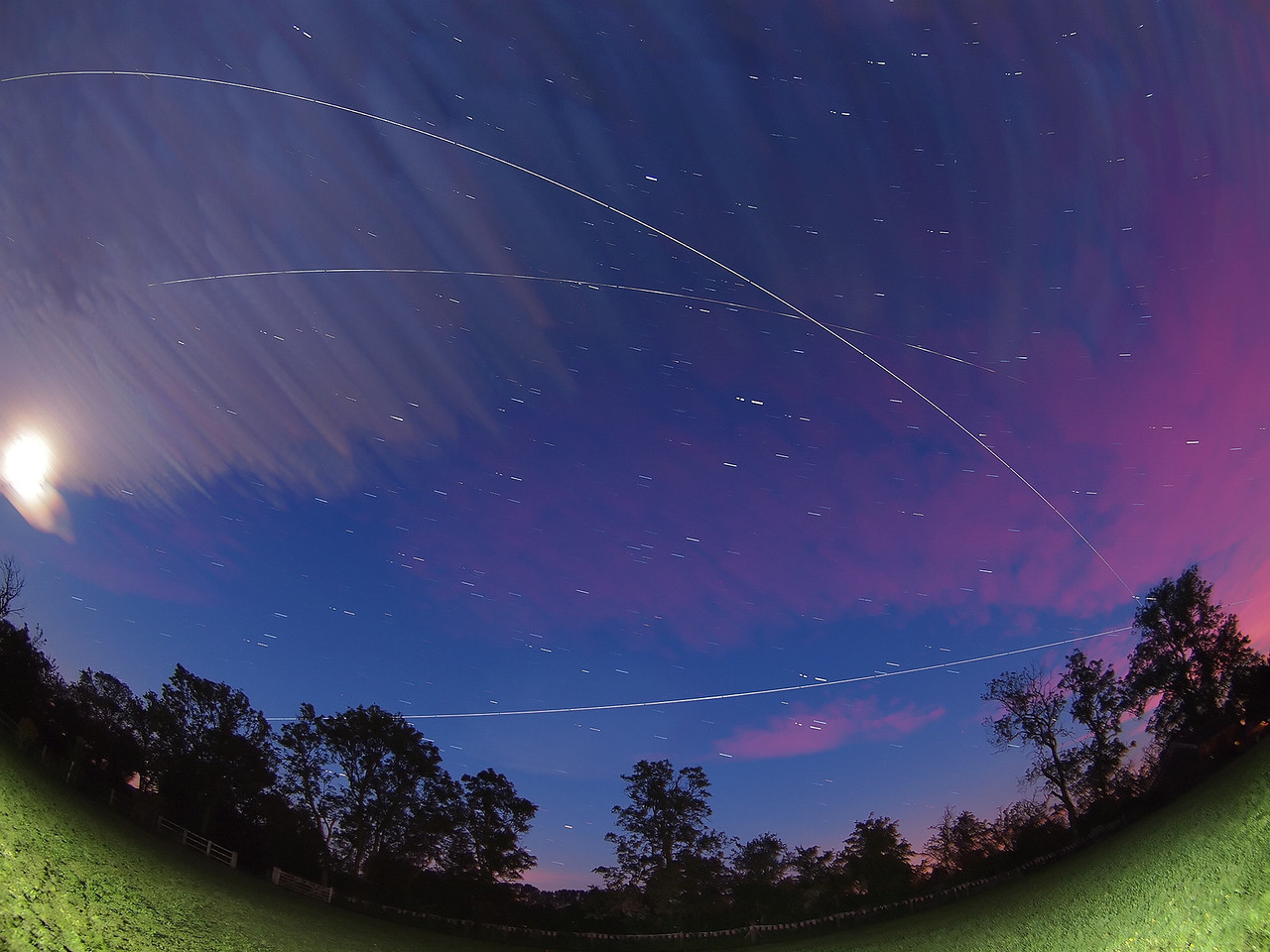 Sat 09th & Sun 10th June 2012. A triple flyby capture of the International Space Station (ISS). There were 4 actual flybys this evening at 2207, 2343, 0119 & 0256 hrs, however the first was clouded out. This shot shows each of the last 3 flybys in one singe composite image. This is how I captured the shot. Firstly I consulted the excellent GoSatWatch app for the exact times of each flyby. I then calculated the best direction to point the camera in order to view all 3 flybys (This was easy since the ISS more or less approached from West and finished East for all.  I therefore bisected and pointed South). I set the camera (Olympus E5) on a tripod with a good wide angle lens (8mm fisheye). Set to Manual mode with an exposure time of 15s and wide open aperture at F3.5, ISO 500 I waited till the first flyby (2343hrs) and forced the camera to shoot continuously (using a remote cable). I added a few bursts of flash just before the first flyby to light up the garden and then left the camera running all night. The following morning I extracted all the images and imported those from each flyby time into stacking software (StarStax) which then produced the final composite of all 3 flybys....Simples :-) The first flyby was exceptionally bright and a shame the cloud rolled in during the second at 0119 hrs which faded the ISS trail. Nice flybys over the moon mind. Summer time offers great opportunities for multiple flyby shots like this. Just prey for clear skies now you know how :-)
