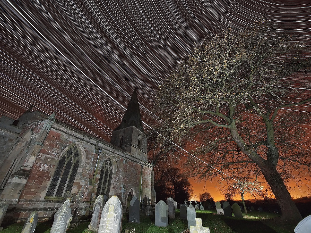 Nov 27/28 2011. As featured in  The Telegraph  and  the Daily Mail   Nov 29th :-) This amazing startrail has captured the ISS, celestial north pole, celestial equator and Jupiter in one shot. 2700 exposures and over 11 hours to execute this shot. A rare clear sky evening during an unsettled and mild start to the British winter. I had this location planned for a while and was just waiting for the right conditions - No cloud, no moon and clear skies. Misterton church with its scary graveyard and this tree make a great foreground composition subject. This is paramount for good startrail shots IMHO. I set up the Olympus E5 with 7-14mm wide angle lens on tripod at F4, ISO 640 and 15s exposure time. Attaching the RM-CB1 cable I locked the cable to take continuous shots all night. Camera was in place approx 1845hrs and I picked it up the following morning at approx 0630hrs. Back at home I imported the 2700 images into StarStax software to provide the final stacked composite. If you look closely between the church spire and tree you will see the International Space Station (ISS) intersecting the startrail arcs. This was the 0555hrs flyby, The stars are spinning around the celestial north star (polaris) top right and just above the church (bottom left) the stars start to reverse direction. This is the celestial equator. Also, the brightest trail line (running through the church spire) is jupiter. Quite an amazing and pleasing shot, if I say so myself :-)