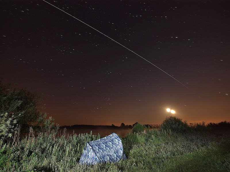 June 11/12 2011. An amazing night of multiple ISS flybys across UK skies. I set up tent and camera waterside and watched all night as the ISS flew over 4 times. This shot shows the 0057hrs flyby over my accommodation ;-) Captured with Oly E3 & 7-14mm.  Camera settings: 15s exposures shot continuous during flyby, ISO 400, F4.