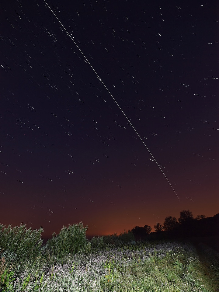 June 11/12 2011. An amazing night of multiple ISS flybys across UK skies. I set up tent and camera waterside and watched all night as the ISS flew over 4 times. This shot shows the 0057hrs flyby in portrait. Captured with Oly E3 & 7-14mm.  Camera settings: 15s exposures shot continuous during flyby, ISO 400, F4.