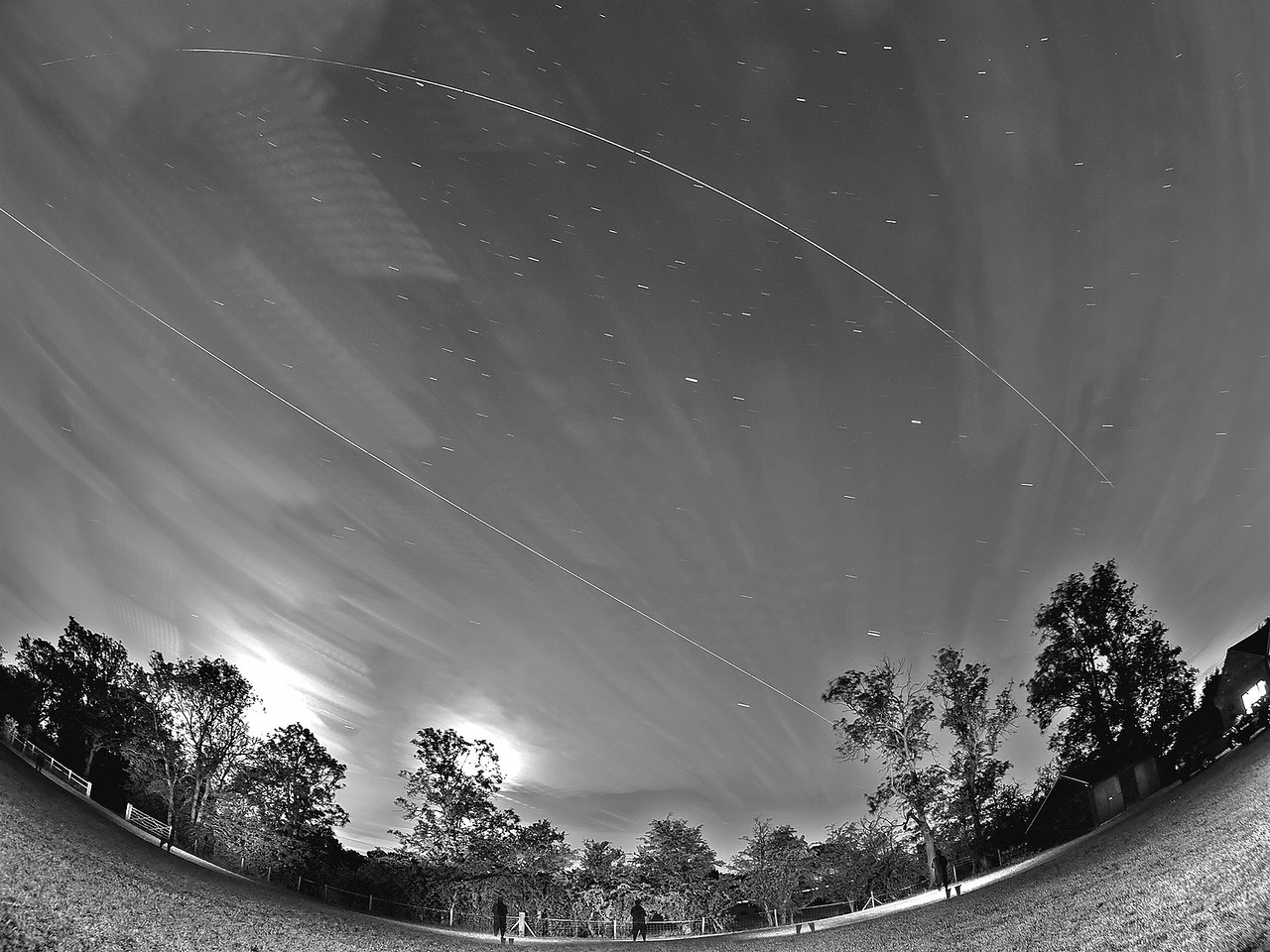 June 14/15 2011. Yet again another amazing marathon night of multiple ISS flybys across UK skies. What a month! This time the ISS flew over 5 times, however light/cloud precluded a few of these from sight. Produced this b&w alternative from a dual Flyby (2313 & 0048 hrs. Again cloud cover rolling in prevented the almost perfect shot.   Why are we getting so many ISS passes in one day? Universe Today Captured with Oly E5 & 8mm fisheye.  Camera settings: 15s exposures shot continuous during flyby, ISO 500, F3.5. Foreground lit with a few flash bursts away from camera.