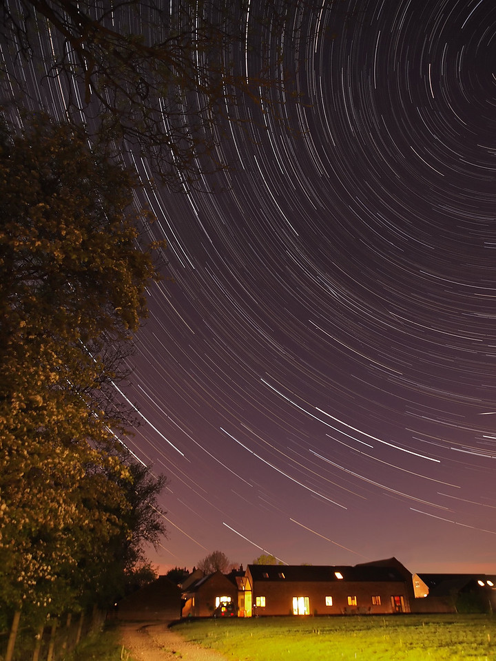 May 12_13 2011. Nice clear evening and perfect for a star trail. Using my barn and the trees as a frame I set my camera out at 2200hrs until the next morning. This shot is a composite of the first 350 images. After this, clouds rolled in and polluted the sky. Spot the meteor at 4 o'clock :-) F2.8, 15s exposures (shot continuous) ISO 400. Captured with Oly E5 & 12-60mm SWD
