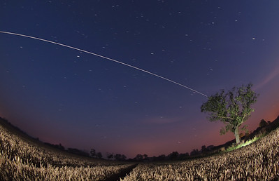 August 10th 2012. 2159 hrs flyby. Great super bright overhead pass originating in South West sky and moving towards due East. Composed against a nice corn field. Captured with Oly E5, 8mm fisheye. Numerous 15s exposures, F3.5 and composite stacked with StarStax software.