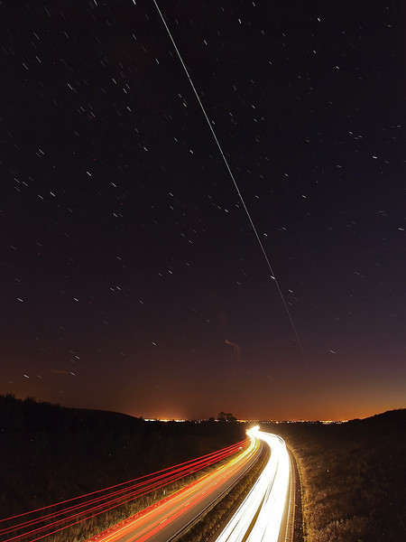 Aug 20 2011. 2146 hrs super bright pass of the ISS. This time we had crystal clear skies :-) Directly overhead so I located my local east/west trunk road and set up the car trails shot with 2 cameras. This one captured with Olympus E3 & 7-14mm. F5, ISO 400 and approx 9 15s exposures stacked to produce this.
