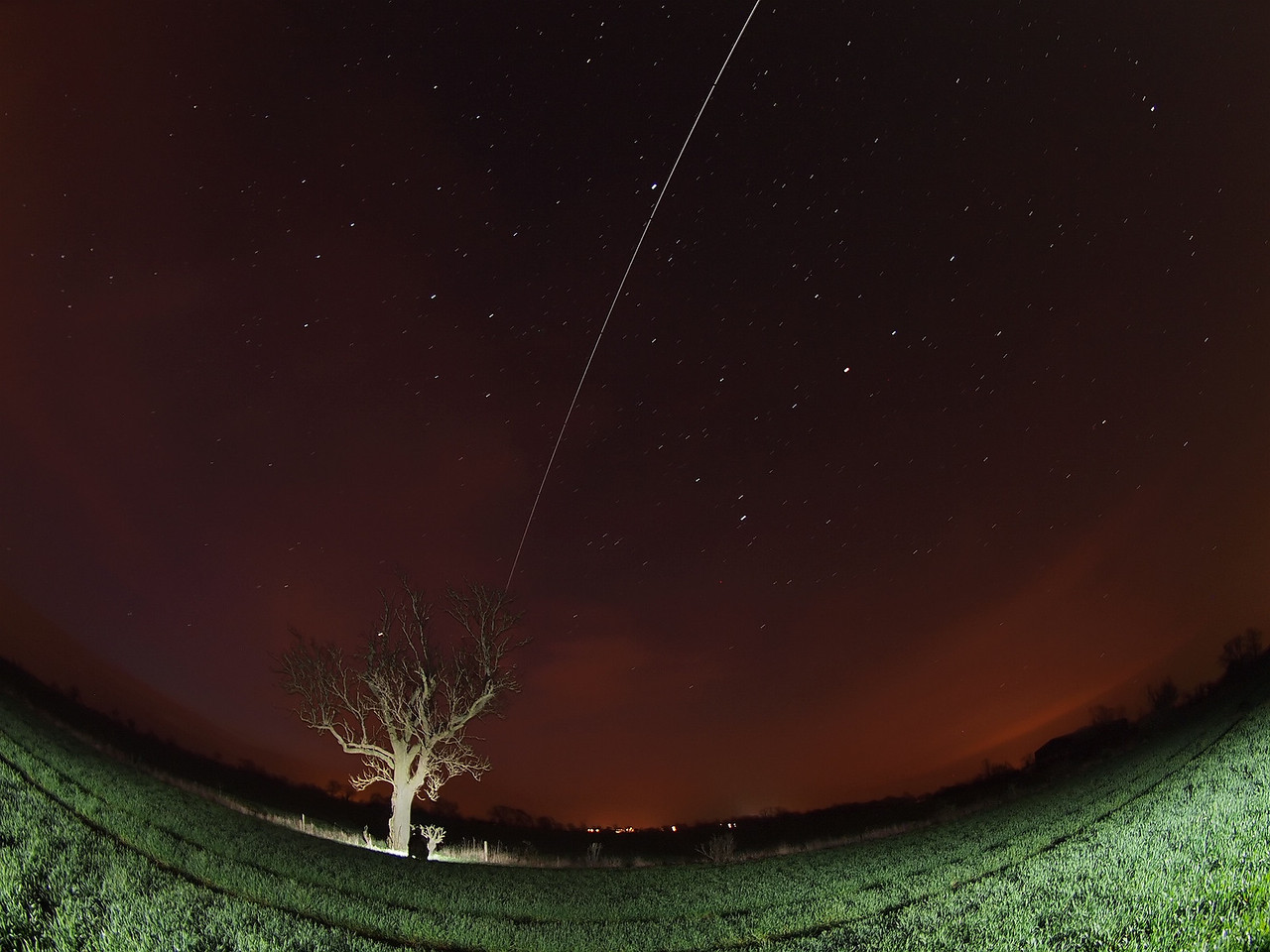 March 29 2012. 0531 hrs ISS pass. Captured with Olympus E5 & 8mm fisheye. Approx half a dozen 15s shots in this final composite. F3.5, ISO 500. Tree and field lit by remote flash.