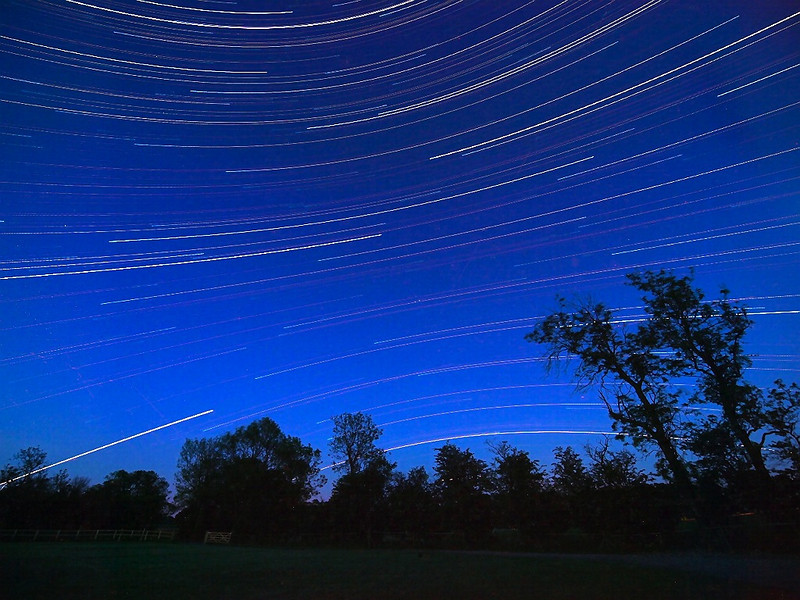 Really pleased with this startrail. Only managing approx 5hrs of darkness because of the long days. Taken between 1030pm and sunrise following day. May 31 2009 in Sth Leics, UK. Love the opposite curvature of the trails above and below the celestial equator. Olympus E3, 7-14mm lens. Just over 1000 exposures stacked in startrails.
