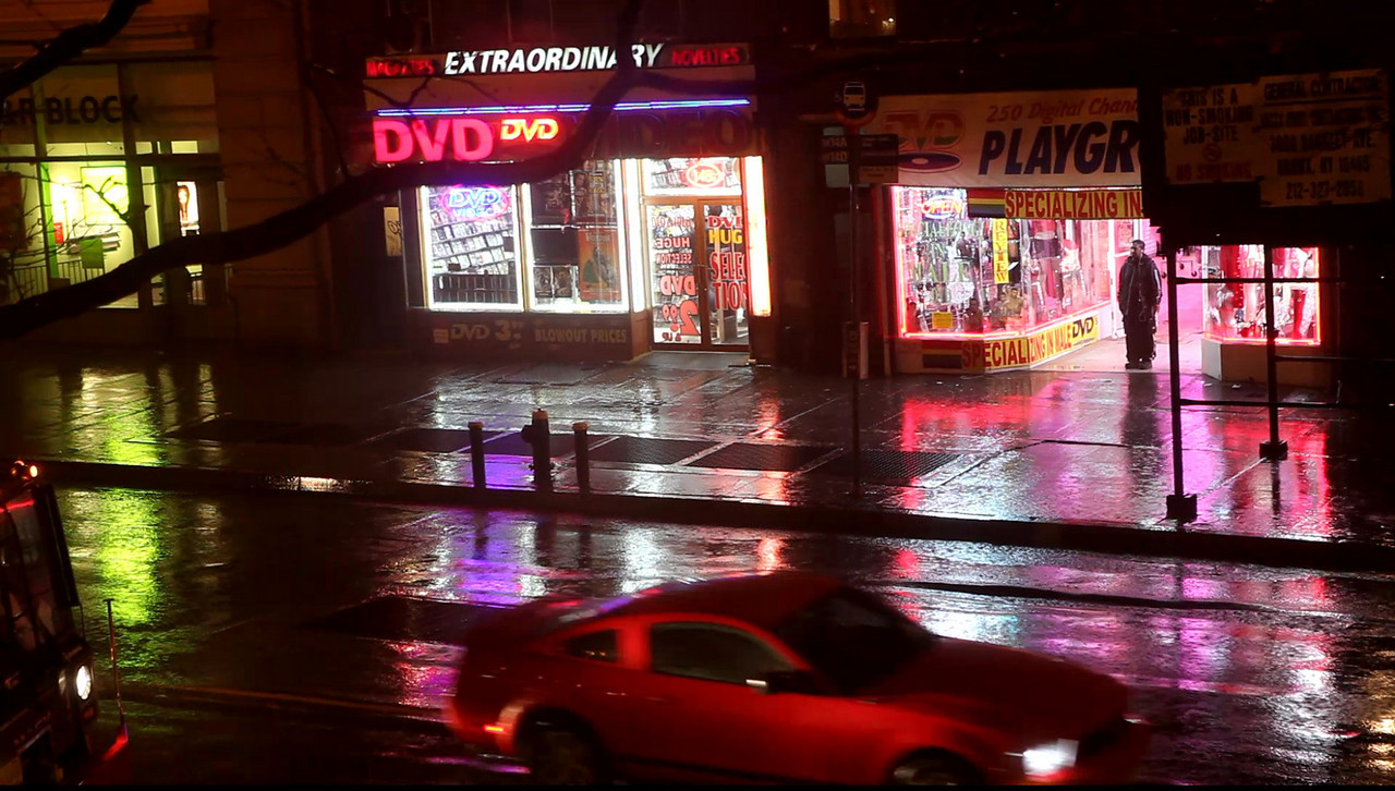 Shots of Sex Shops in the rain at night sans Sex.<br /> Through the window
