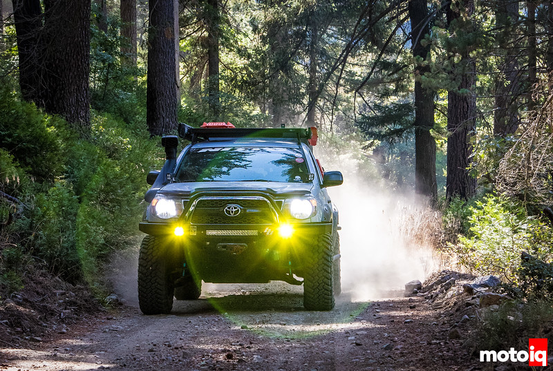 Jimahajer Garage Tacoma kicking up dust on a trail, coming with headlights and fog lights on