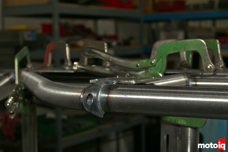 close up of bare aluminum tubing with clamps holding pieces for welding, weld beads visible on some components