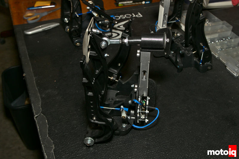 back side of tilton pedal assembly with load cell and other electronics attached, bright blue wires visible