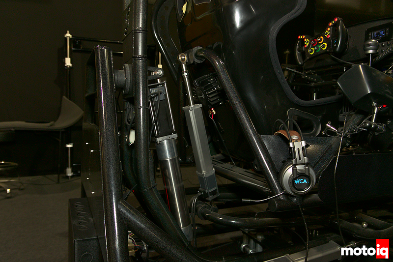 linear actuators attached to cockpit tubes with racing seat and steering wheel visible to the right