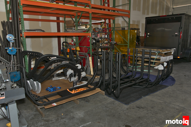 black powdercoated tubing assemblies neatly stacked with orange warehouse shelving and a trailer in the background