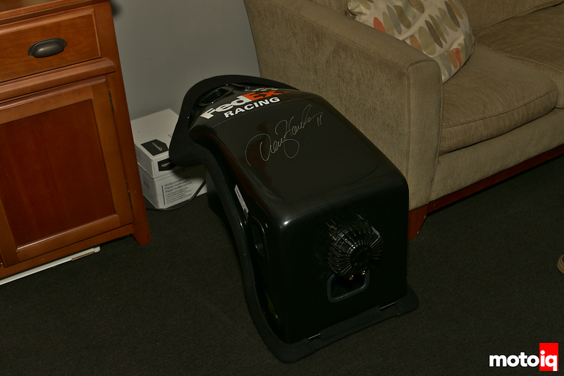 racing seat laying face down on floor with FedEx racing sticker and autograph on back, with speaker/transducer visible bolted to bottom of seat