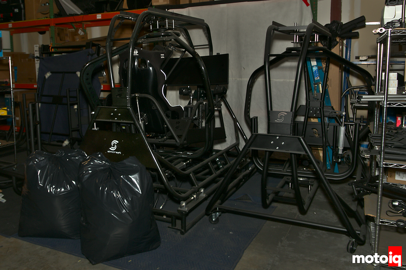 two partially assembled sim racing cockpits made of tubular steel