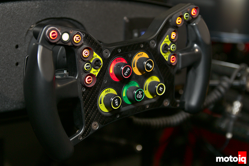 LMP-style sim racing wheel with adjustable dials, back-lit buttons, and tiny joysticks