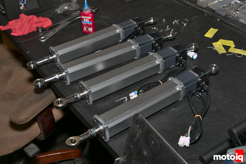 four silver and grey linear actuators with rod ends laying on a table