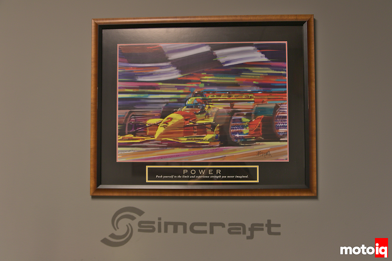 simcraft logo decal on a wall underneath a formula car painting