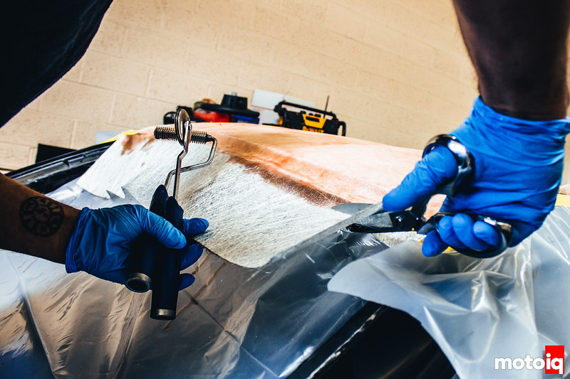 Once covered in epoxy, the excess fiberglass is trimmed away, and the remaining sheet is pressed down using metal rollers to ensure all the crevices are seated properly, with no air bubbles.