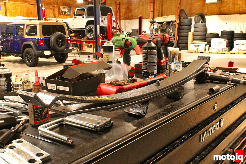 stack of helper leaf springs on work bench with scattered supplies around